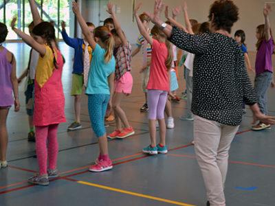 Schülerinnen und Schüler der Grundschule tanzen in der Sporthalle
