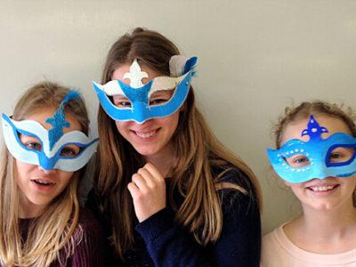 Kunst-AG - drei Schülerinnen mit selbst gebastelten Masken