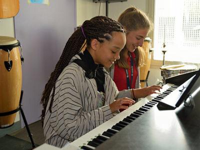 Zwei Schülerinnen spielen gemeinsam Klavier